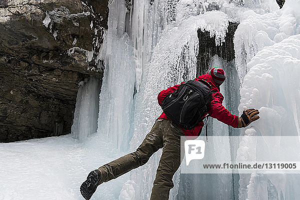 Rear view of man with backpack standing by frozen waterfall over mountain