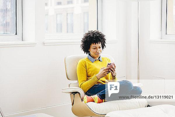 Geschäftsfrau in voller Länge  die ein Smartphone benutzt  während sie im Büro auf einem Stuhl sitzt