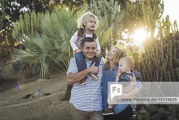 Eltern mit Söhnen stehen im Park vor Pflanzen