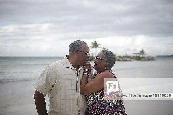 Glückliches älteres Ehepaar am Strand vor bewölktem Himmel