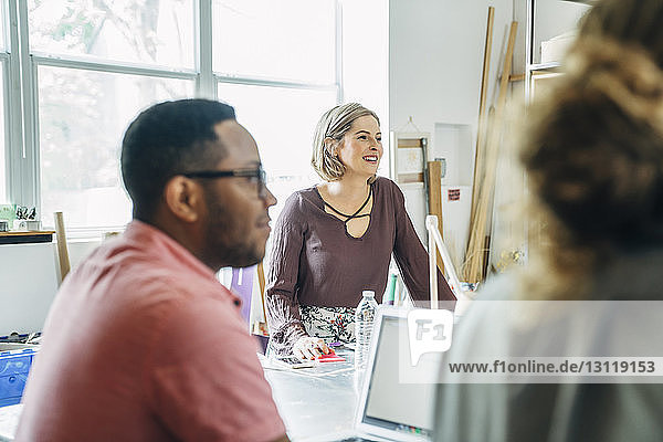 Happy businesswoman looking away with male colleagues sitting in foreground