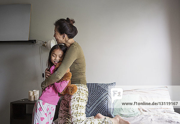 Mother embracing girl on bed at home