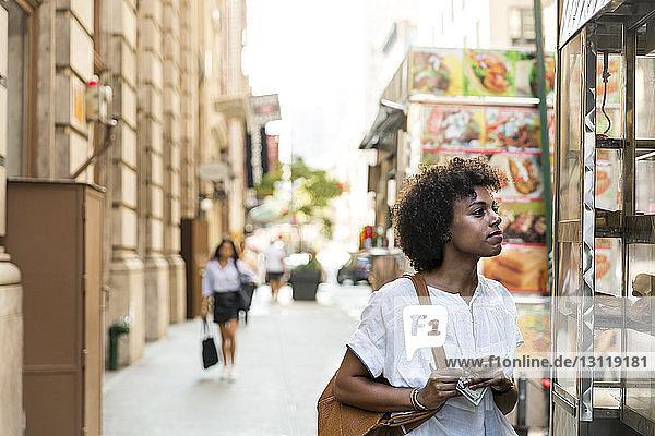 Nachdenkliche Frau hält Papiergeld,  während sie in der Stadt im Laden steht