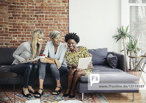 Fröhliche Geschäftsfrauen  die im Kreativbüro auf dem Sofa sitzend einen Tablet-Computer benutzen