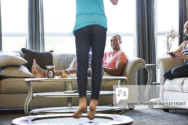 Eltern sehen Tochter zu Hause auf dem Trampolin springen