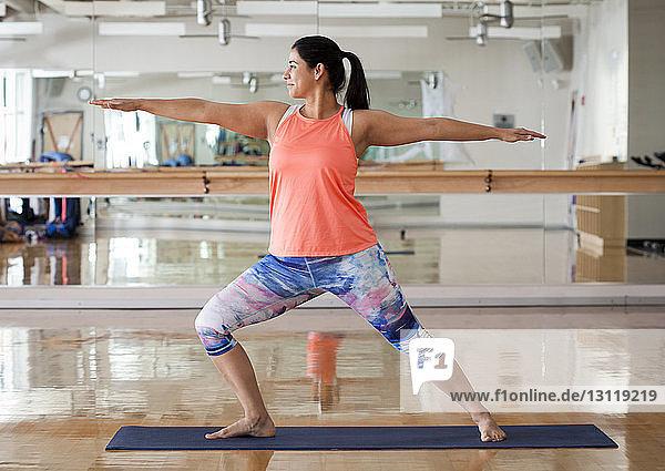 Frau in voller Länge in Warrior-2-Pose beim Training im Fitnessstudio