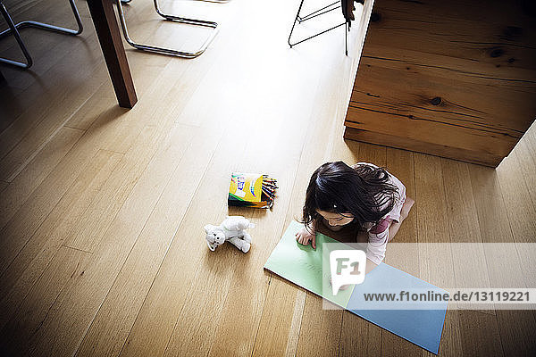 High angle view of girl studying on wooden flooring at home