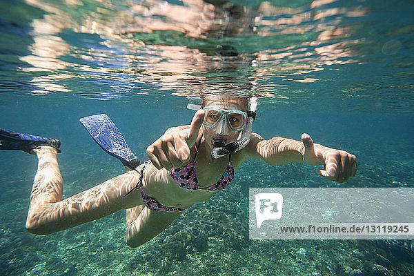 Porträt einer erfolgreichen Frau  die beim Schnorcheln im Meer die Daumen nach oben zeigt