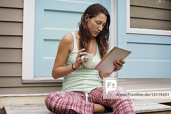 Junge Frau benutzt Tablet-Computer vor dem Haus  während sie eine Kaffeetasse hält