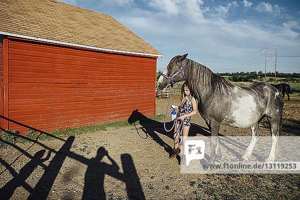 Mädchen hält Sprühflasche  während sie zu Pferd am Stall steht