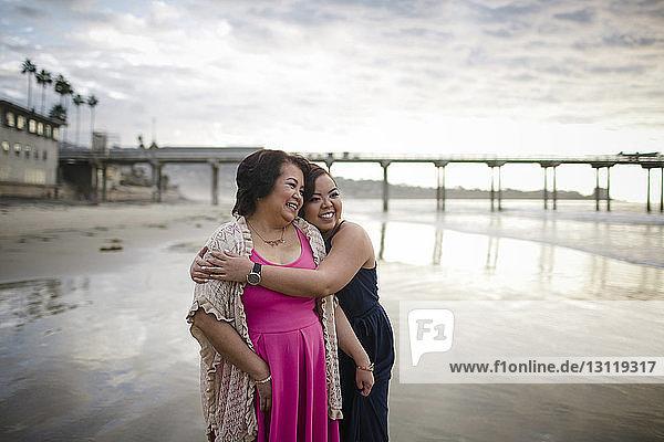 Glückliche Frau umarmt Mutter  während sie am Strand vor bewölktem Himmel steht