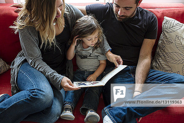 High angle view of family looking at picture book while sitting on sofa at home