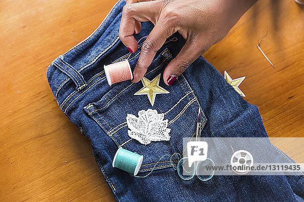 Geschnittene Hand einer Frau  die bei Tisch sternförmige Textilaufnäher an Jeans anpasst