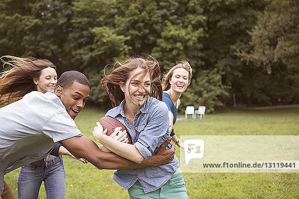 Man pulling woman holding football ball while friends running in background on field