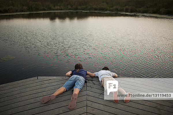 High angle view of carefree siblings lying on pier over lake at park