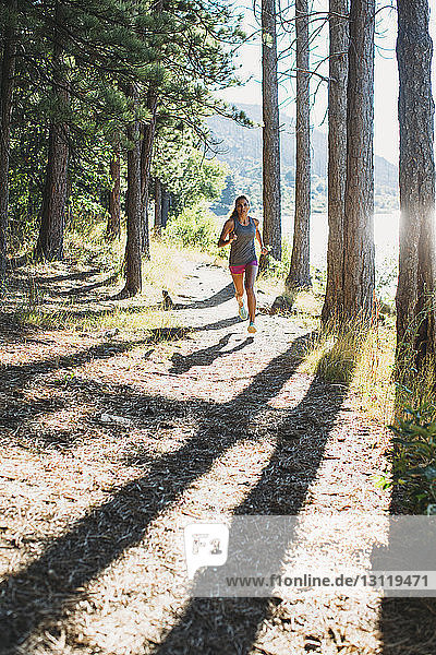Frau rennt am sonnigen Tag an Bäumen vorbei auf dem Pfad