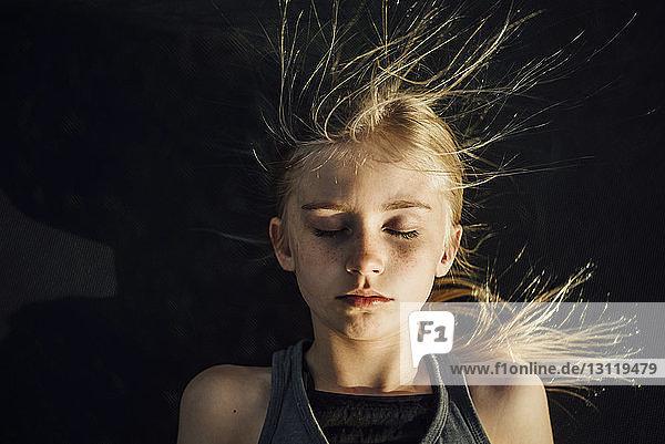 Draufsicht eines Mädchens mit geschlossenen Augen und zerzaustem Haar bei sonnigem Wetter