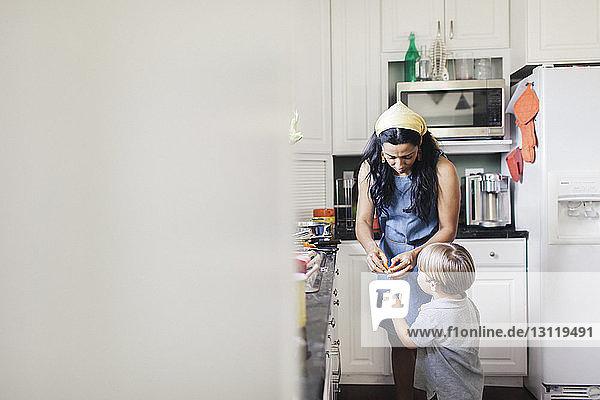 Mutter gibt dem Sohn eine Kirschtomate  während er in der Küche steht