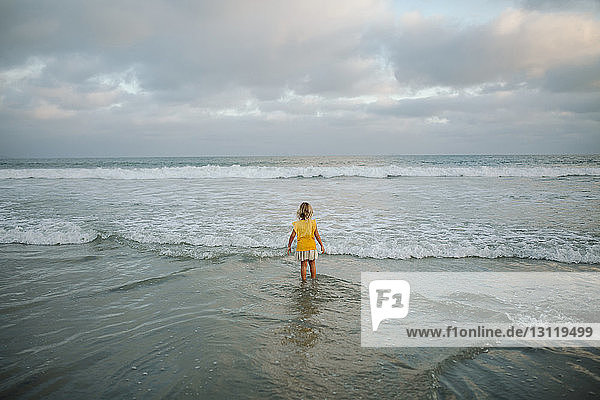 High angle view of carefree girl standing in sea at beach against cloudy sky