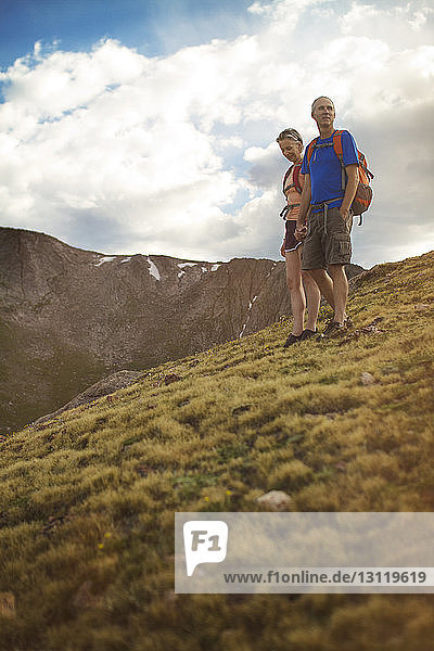 Low angle view of couple standing on mountain against cloudy sky