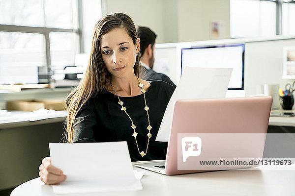 Geschäftsfrau liest Dokument bei der Arbeit im Büro