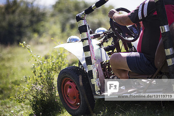 Midsection of man riding off-road vehicle on field