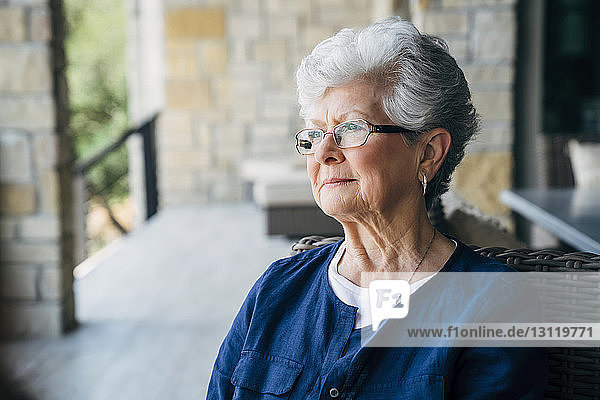 Thoughtful senior woman sitting on porch