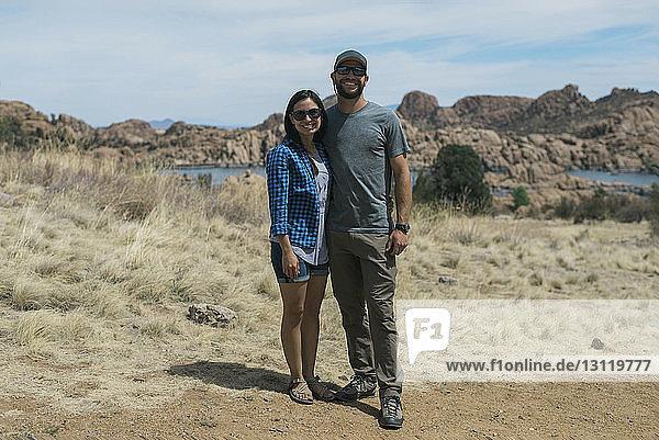 Porträt eines glücklichen Paares mit Sonnenbrille  das auf dem Feld vor bewölktem Himmel steht