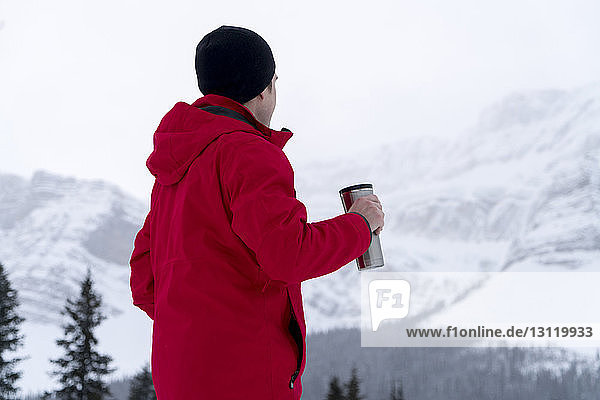 Side view of hiker having drink during foggy weather
