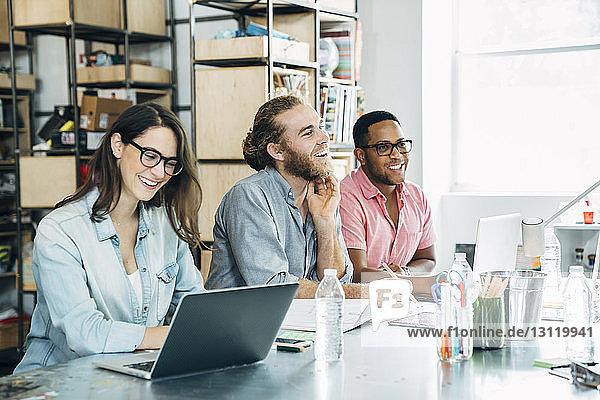 Glückliche Geschäftsfrau benutzt Laptop-Computer  während männliche Kollegen wegschauen