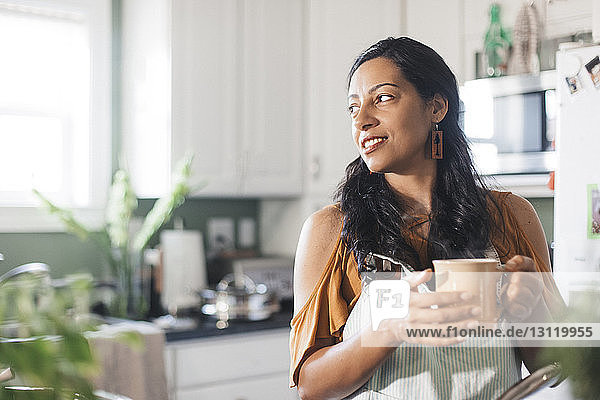 Woman looking away while holding coffee cup in kitchen