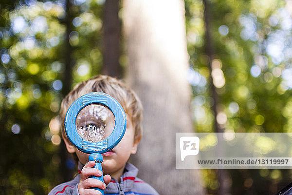 Junge schaut durch eine Lupe  während er im Wald steht