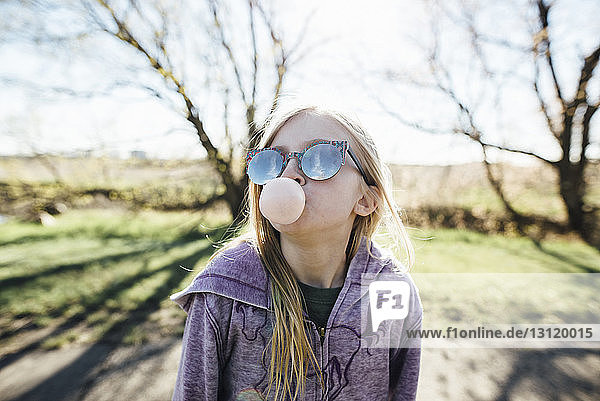 Girl wearing sunglasses blowing bubble gum while standing on road against sky
