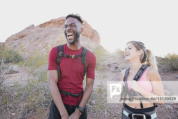 Glückliche Freunde mit Rucksäcken  die lachen  während sie vor Felsformationen stehen