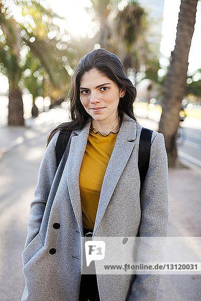 Porträt einer selbstbewussten jungen Frau  die in der Stadt stehend einen Mantel trägt