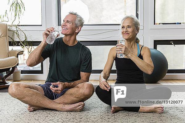 Lächelndes Paar trinkt beim Sport zu Hause Wasser aus Flaschen