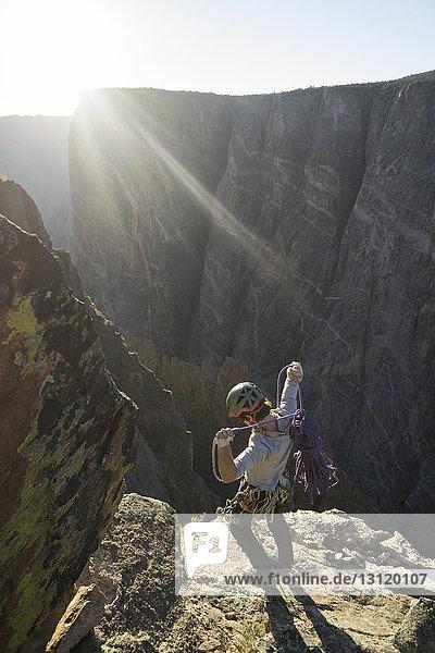 Hochwinkelaufnahme eines Mannes mit Seil  der am sonnigen Tag auf einem Berg gegen den Himmel steht