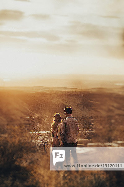 Rear view of young couple standing on field during sunset