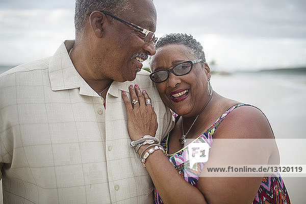Glückliches älteres Ehepaar steht am Strand vor bewölktem Himmel