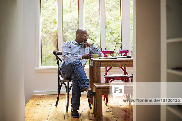 Senior man using laptop while having coffee at home