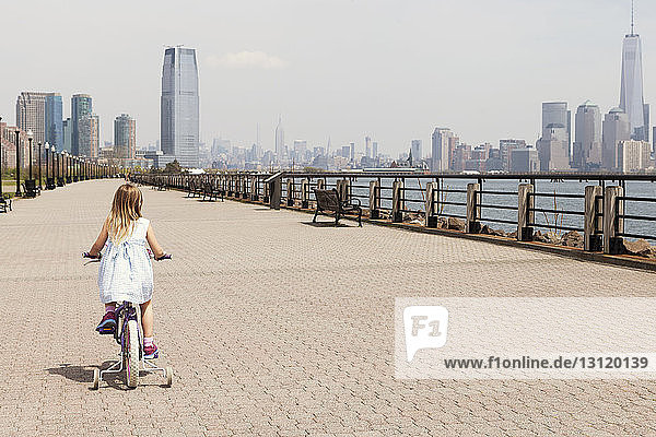 Rear view of girl cycling on promenade with city skyline in background