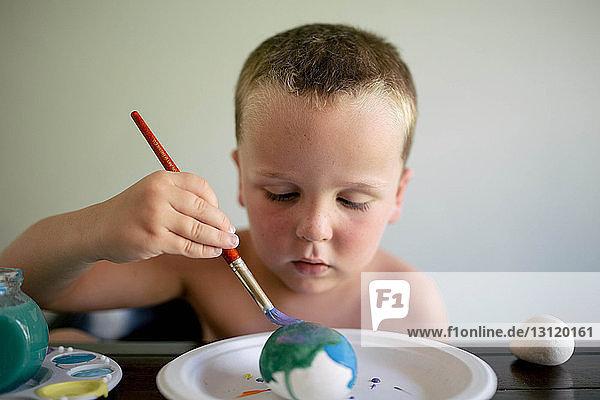 Junge ohne Hemd färbt Ostereier  während er zu Hause am Tisch sitzt