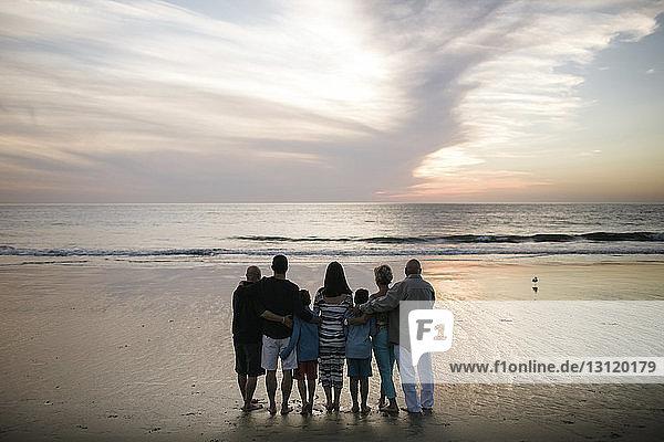 Rückansicht einer Familie  die bei Sonnenuntergang am Strand vor bewölktem Himmel steht
