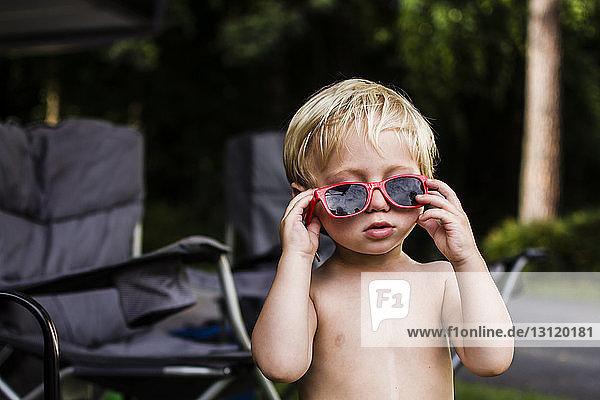 Süßer Junge ohne Hemd mit Sonnenbrille  der im Hinterhof steht