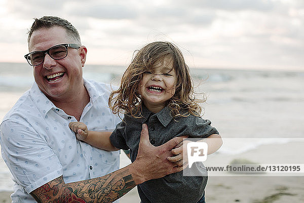Cheerful father holding son at beach