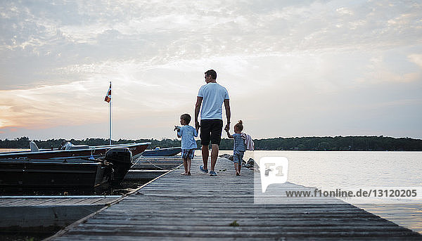 Rear view of father and children walking on pier against cloudy sky