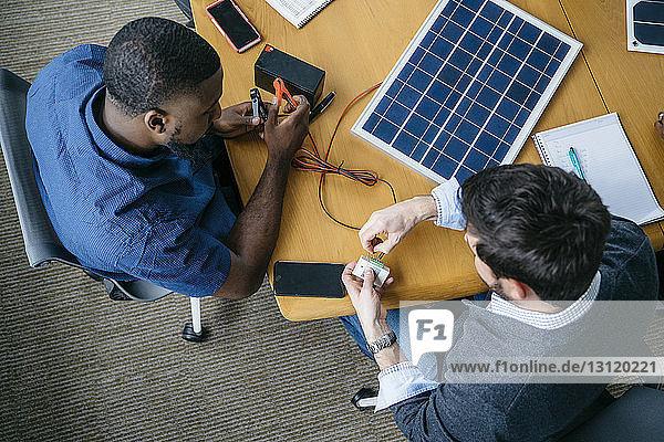 Draufsicht auf Geschäftsleute  die im Büro am Solarpanel-Modell arbeiten