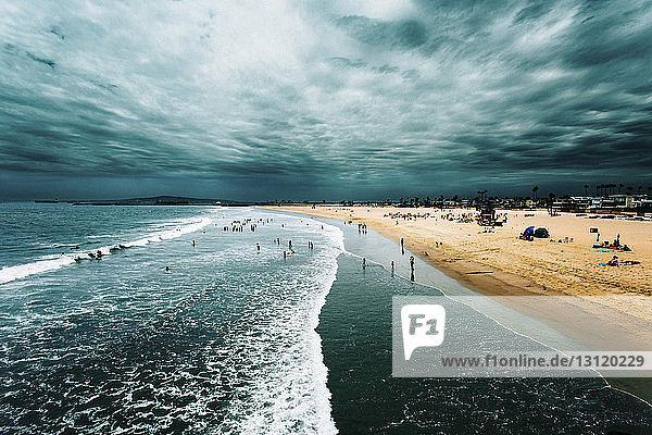 Menschen am Strand gegen bewölkten Himmel
