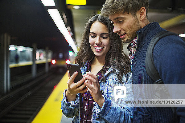 Couple using mobile phone while standing at subway station