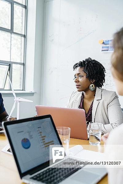 Geschäftsleute mit Laptop-Computern am Tisch im Büro